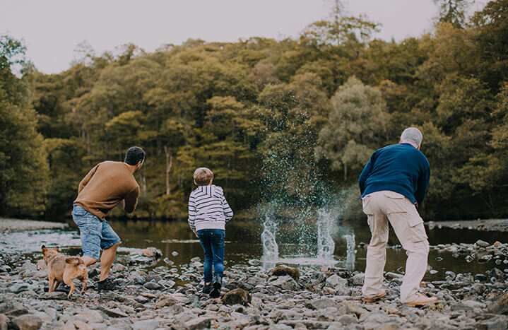 grandfarther-farther-and-son-having-fun-skimming-rocks-at-lowther-castle