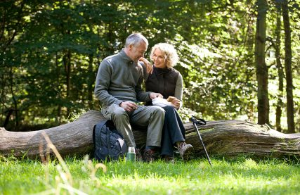 couple-having-a-picnic-together-on-a-tree-trunk